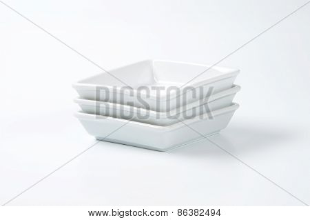 stack of white square plates on white background