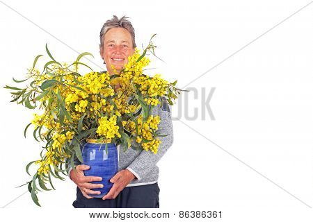 Beautiful mature woman with a vase of mimosa blossoming