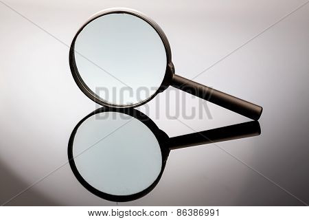 a magnifying glass is on a gray background and reflected