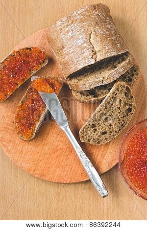 Red caviar toasts sandwich with silver knife, bowl of tasty red caviar with spoon and fresh baked ho