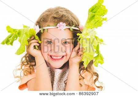 Beautiful healthy little curly girl enjoying playing with lettuce leaves