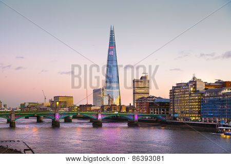 LONDON, UK - DECEMBER 19, 2014: Shard of glass in the dusk. City of London business aria. Thames vie