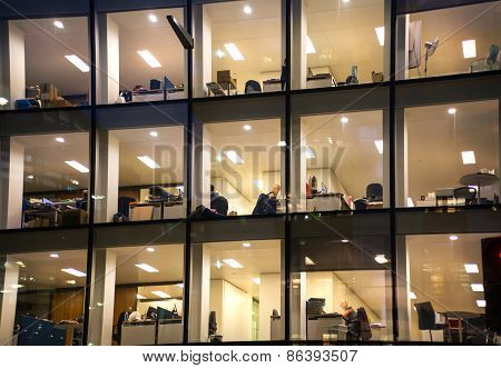 LONDON, UK - DECEMBER 19, 2014: Office block with lots of lit up windows and late office workers ins