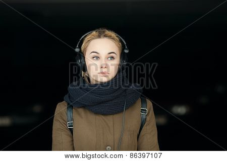 Outdoors portrait of young beautiful blonde hipster woman in big dj headphones