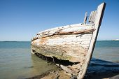 image of bluff  - Derelict wooden oyster boat left rot away to on beach at Ocean Beach Road - JPG