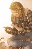 stock photo of dreadlocks  - freelance dreadlocks guy sitting with digital tablet typing message warm filter applied - JPG