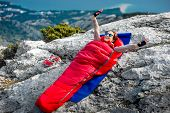 picture of sleeping bag  - Young woman waking up in red sleeping bag on the rocky mountain - JPG