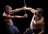 picture of filipino  - two muscular martial artists sparring on a black background - JPG
