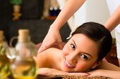 stock photo of massage oil  - Chinese Asian woman in wellness beauty spa having aroma therapy massage with essential oil - JPG