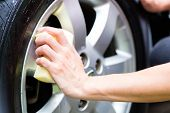 stock photo of cleaning house  - man cleaning wheel rim while car wash - JPG