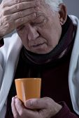 pic of high fever  - Senior sick man with high temperature drinking hot tea