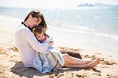 stock photo of babysitter  - Young Hispanic mother relaxing at the beach and embracing her little daughter on a sunny day - JPG
