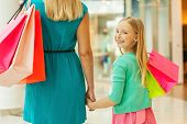 stock photo of shoulders  - Rear view of mother and daughter holding shopping bags while little girl looking over shoulder and smiling - JPG