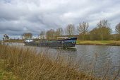 image of barge  - Barge sailing in a canal under a cloudy sky in spring