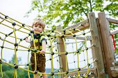image of playground  - Cute kid boy having fun with climbing on children playground outdoors on warm summer day - JPG