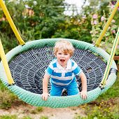image of swing  - Funny happy kid boy having fun chain swing on outdoor playground - JPG
