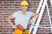 image of step-ladder  - Technician holding drill machine while leaning on step ladder against red brick wall - JPG