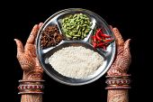 stock photo of mehendi  - Woman hands with henna holding plate with rice and spices isolated on black background with clipping path - JPG