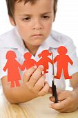 stock photo of divorce-papers  - Sad kid cutting his paper people family  - JPG