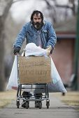 picture of possess  - Homeless man with beard pushing a shopping cart with all his possessions - JPG