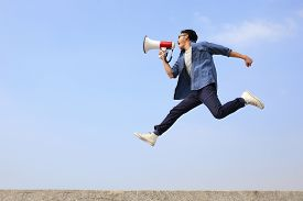 picture of shout  - man jump and shout by megaphone with blue sky background asian - JPG