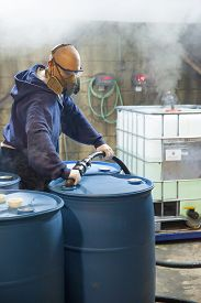 foto of respirator  - Chemical Plant. Man working in protective gear safety glasses respirator and gloves blends chemicals in 55 gallon drums. Gasses from chemicals emit from the containers. Corrosive Environment. ** Note: Visible grain at 100%, best at smaller sizes - JPG