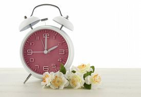 picture of time-saving  - Daylight Saving Time concept with spring theme pink retro style alarm clock on white wood background - JPG