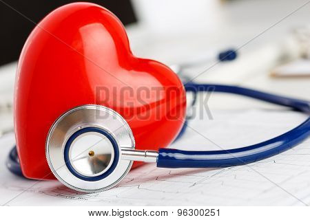 Medical Stethoscope And Red Toy Heart Lying On Cardiogram Chart Closeup