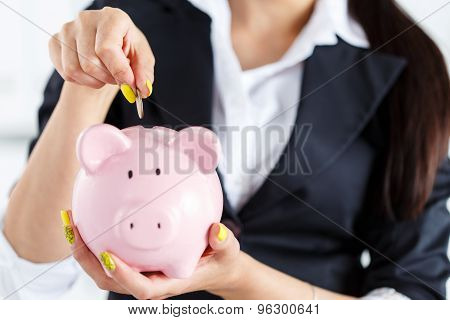 Business Woman Putting Pin Money Coins Into Pink Piggybank Slot