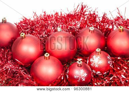 Several Red Christmas Baubles And Tinsel Isolated