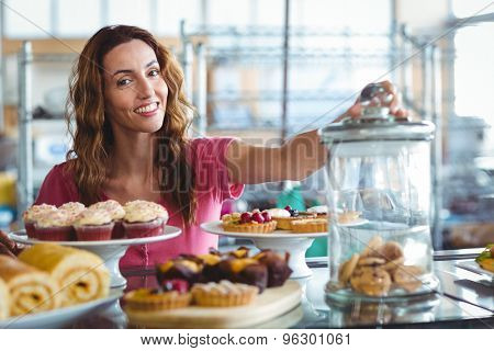 Pretty brunette smiling at camera behind plates of pastries at the bakery