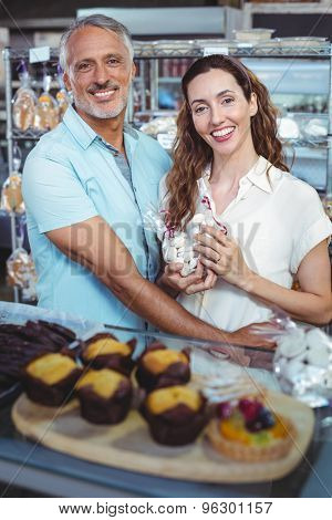 Cute couple looking at camera and standing arm around in the bakery store