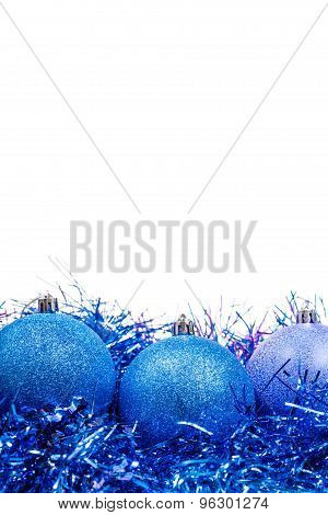 Three Blue Xmas Balls At Tinsel Close Up Isolated