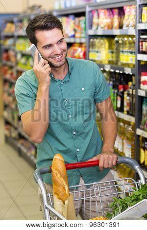 Smiling man buy food and phoning at supermatket