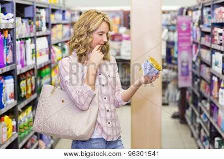 Side view of a pretty blonde woma looking at a product in supermarket