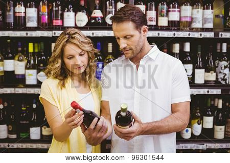 Casual couple looking at wine bottle in supermarket