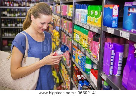 Thoughtful pretty brunette looking at product in shelf in supermarket
