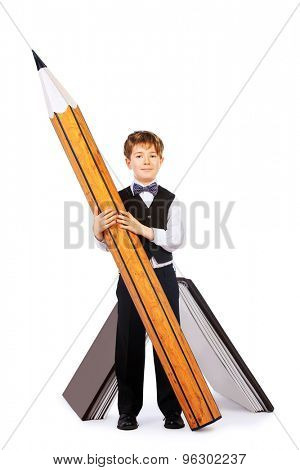 A boy stands with a huge pencil and huge book. Educational concept. Isolated over white.