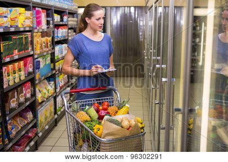 Pretty woman looking at product on freezer at supermarket