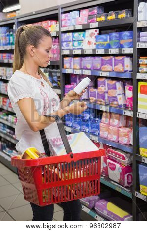 Woman taking a bottle of pills in the shelf of aisle at supermarket