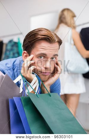 A bored man with his hands under his chin in the clothing store