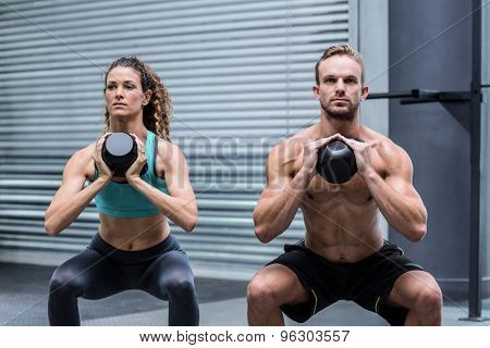Kneeling muscular couple exercising with kettlebells
