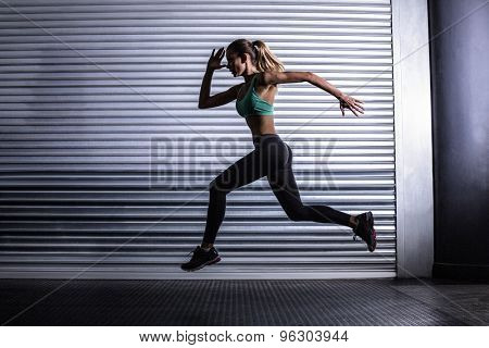 Side view of a muscular woman running in exercise room