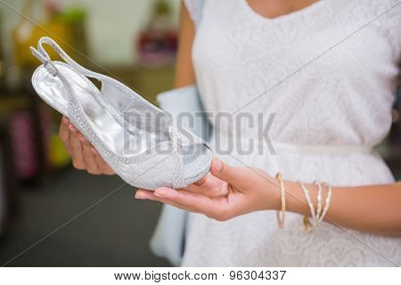 Woman looking at high-heeled sandals at a shoe shop