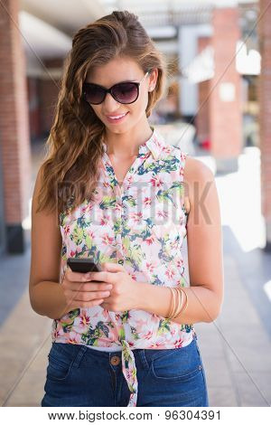 Smiling woman with sunglasses using smartphone at the shopping mall