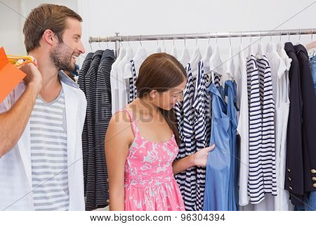 Smiling couple looking at clothes at a boutique