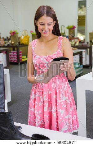 Young happy woman looking at a shoe in a shoe store