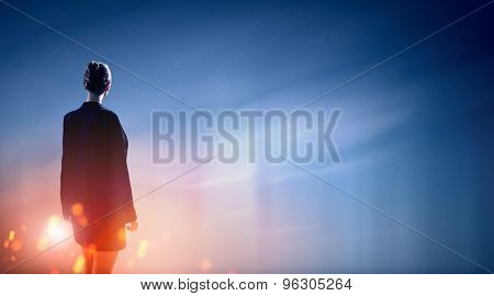 Back view of businesswoman against mountain landscape looking far away