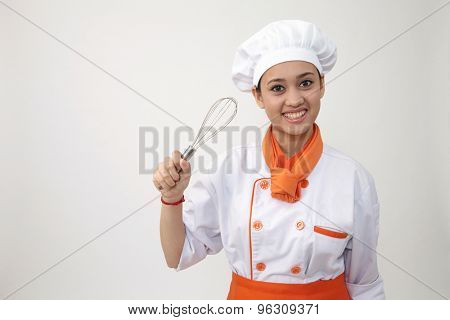 Portrait of a Indian woman with chef uniform holding whisk