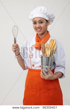 Portrait of a Indian woman with chef uniform holding whisk and spatula